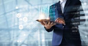 Geschäftsmann mit einem Tablet, über dem ein Hologramm mit Verkaufsdaten und Wirtschaftswachstum angezeigt wird.