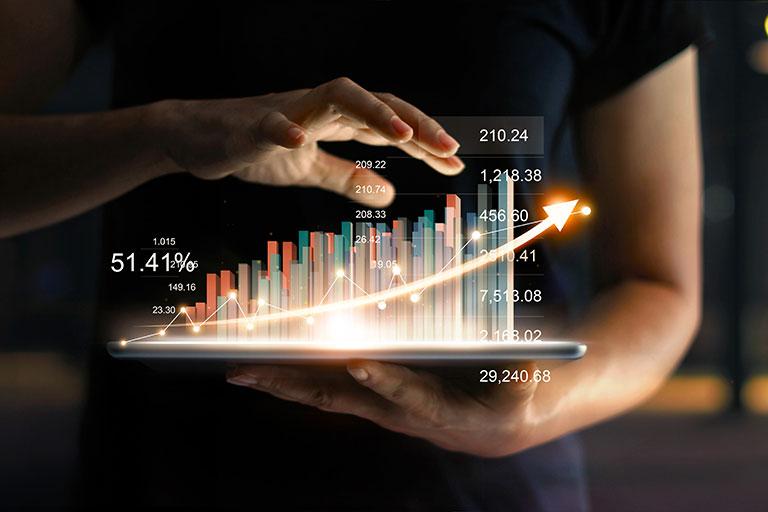 Geschäftsmann, der ein Tablet hält, auf dem eine virtuelle Statistik mit Pfeil nach oben zu sehen sind