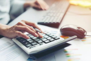 Großaufnahme von Hand einer Geschäftsfrau, die Berechnungen mit Hilfe des Taschenrechners macht