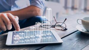 Geschäftsmann, der ein wachsendes 3D-Diagramm über einem Tablet analysiert