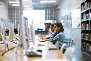 Universitätsstudenten, die in der Bibliothek auf Computern arbeiten