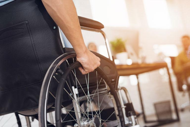 Ein invalider Mann sitzt in einem Rollstuhl