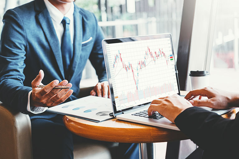 Business Team diskutiert und analysiert die Grafik des Außenhandels