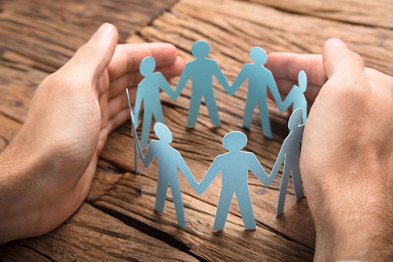 Nahaufnahme von Händen, die ein Team von Papiermännchen umgeben.